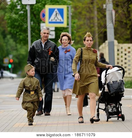 Orel Russia - May 9 2017: Victory Day selebration. Young mother and child in war uniform outfit with baby stroller walking along the street