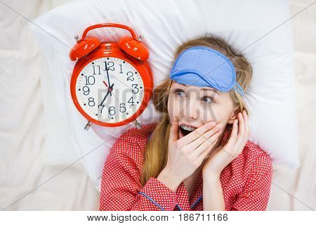 Shocked Woman Wearing Pajamas Holding Clock Overslept