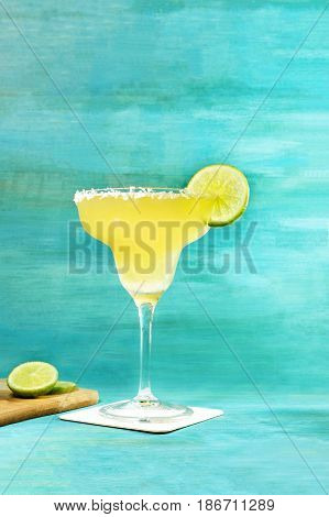 Lemon Margarita cocktail with a wedge of lime on a vibrant turquoise background with copy space, selective focus