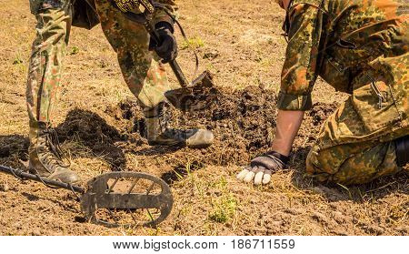 Guys in camouflage dig a hole under the bright sun it's their hobby they are looking for the echo of war