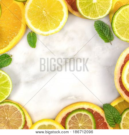 A vibrant square frame of juicy citrus fruits, on a white marble texture, with copy space. Grapefruit, lime, lemon, and orange slices with mint leaves