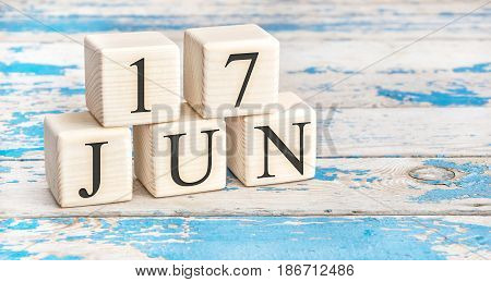 June 17th. Wooden cubes with date of 17 June on old blue wooden background.