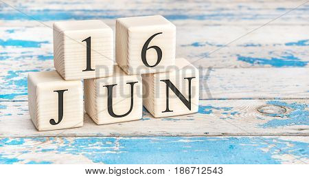 June 16th. Wooden cubes with date of 16 June on old blue wooden background.