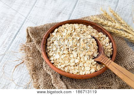 Rolled oats, oat flakes, uncooked oats in bowl with wooden spoon and wheat ears. Concept of healthy eating, vegan food, healthy food, breakfast.