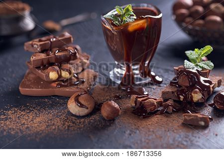 Homemade hazelnut spread or hot chocolate in glass bowl with nuts and chocolate bar. Cocoa powder nuts and chocolate background. Ingredients for cooking homemade chocolate sweets. Sweets concept.