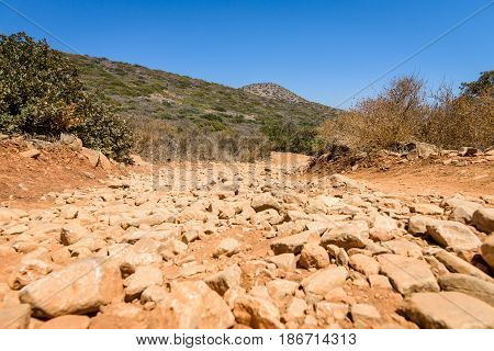 The dirt road strewn with large stones. The peninsula Kalydon. Crete. Greece.