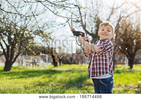 Look at me, daddy. Cute hazel-eyed child wearing a red plaid shirt cutting the tree branches with a pride look and smiling at camera