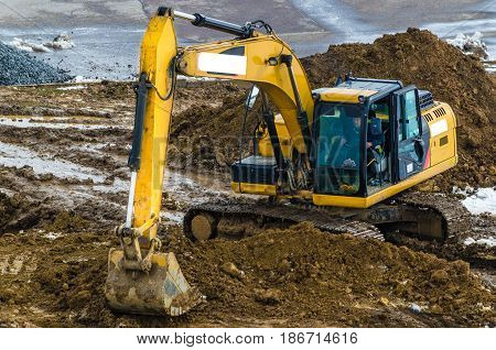 Yellow excavator illuminated by the sun produces earthworks