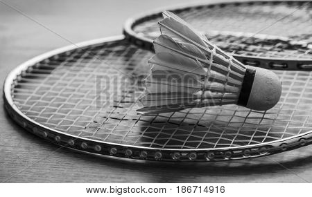Badminton ball (shuttlecock) and racket on court floor. Black and white. White color badminton ball. Two badminton racket. Badminton ball with selective focus.