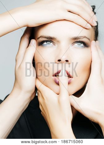 beautiful woman with fashion makeup on pretty face and hands on head hold finger on mouth or lips