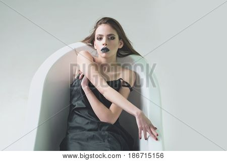 bath. pretty young caucasian brunette girl in dress with long hair and black lipstick on lips lying in bath tub in bathroom in dress isolated on grey background copy space