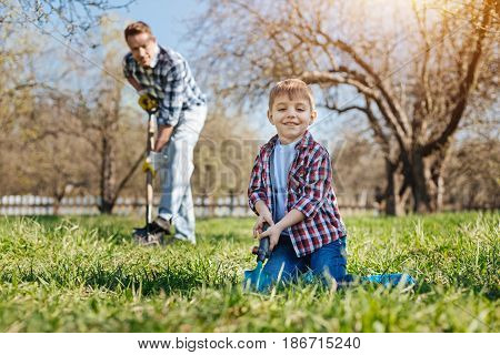 Team work. Two male family members enjoying the weekends outdoors in a garden, digging the soil and planting the apple trees