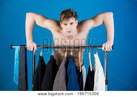 Shaved Man With Naked Muscular Torso Standing At Wardrobe Hanger