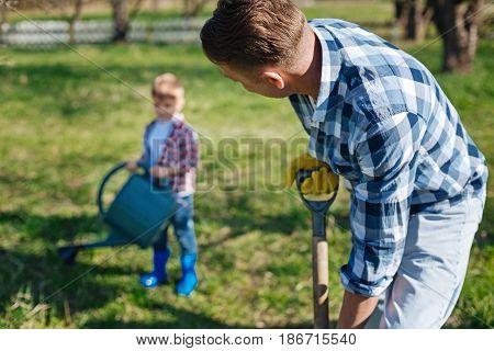 Amateur gardeners. Adult man with a spade watching his adorable child watering a green vernal lawn with a pouring can while gardening together