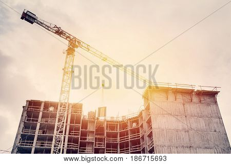 Large construction site including one cranes working on a building complex, with clear blue sky and the sun.