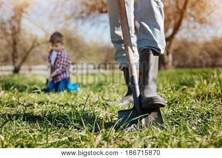 Working hard in garden. Adult man wearing green wellies digging the soil with a shovel while spending free time outside with his grandson