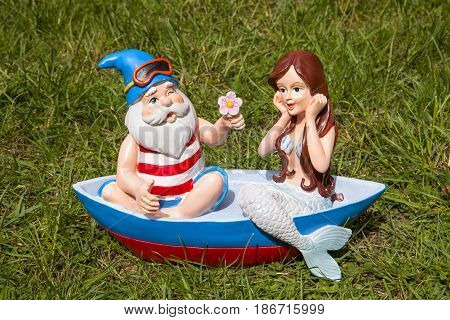 A boat lawn ornament with a gnome and a mermaid