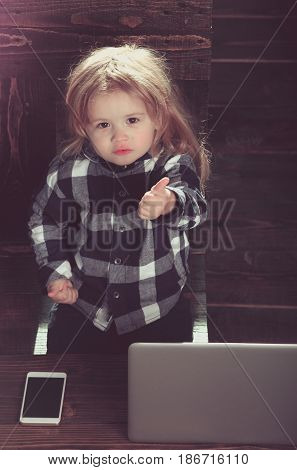 child or small cute business boy with phone and computer in office showing thumb up