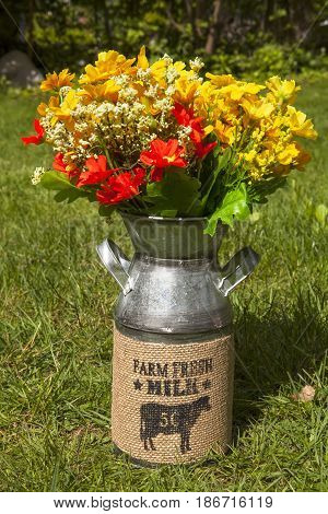 A rustic milk can with flowers for decorating the home