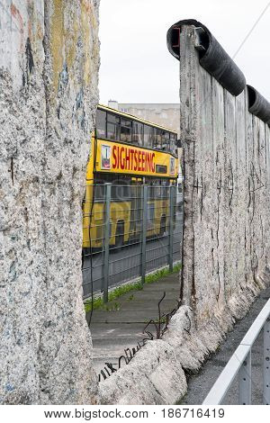 BERLIN GERMANY - APRIL 7: Berlin wall in museum Topography of Terror and yellow sightseeing bus on April 7 2017 in Berlin