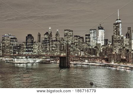 HDR view of Lower Manhattan with Brooklyn Bridge at night.