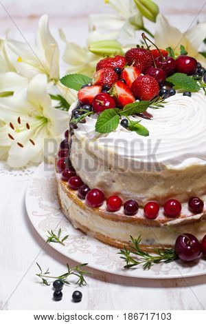 Delicious summer cake with berries and meringue on white wooden background. Homemade cake. Pavlova meringue cake with cream and berries