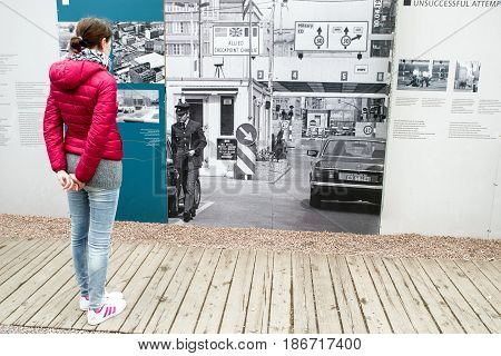 BERLIN GERMANY - APRIL 7: Woman looking on photography of Checkpoint Charlie in open-air museum on April 7 2017 in Berlin