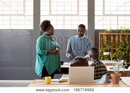 Three casually dressed young African work colleagues drinking coffee and discussing paperwork together while standing in a large modern office