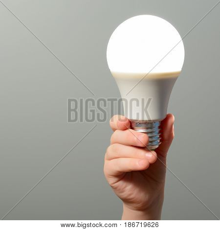 Children's Hand Holds A Glowing Led Bulb