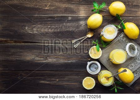 Fresh homemade lemon curd in glass jars on rustic wooden background. Top view. Copy space area.