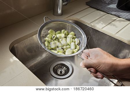 A man's hand holds a sieve with peeled beans over a sink in the kitchen