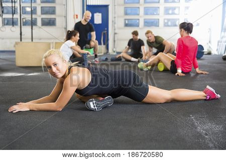 Full length portrait of determined female athlete doing stretching exercise with friends in background at health club