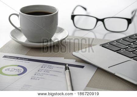 Modern workplace: a prestigious laptop analytical prints with graphs and digital data elegant pen glasses and a cup of coffee
