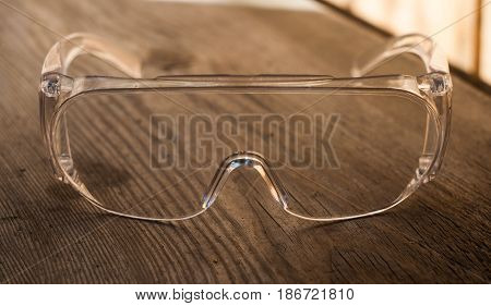 protective transparent plastic glasses on a wooden background, closeup