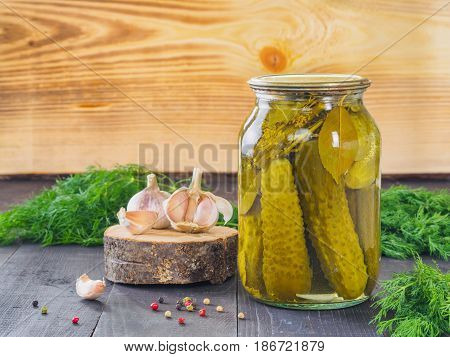 Pickled cucumbers on wooden background. Pickles in glass jar with garlic, peppercorn and fresh dill. Salted cucumber in jar with copy space