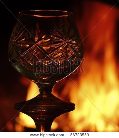 Contours and glare of a crystal glass against the background of a burning fire