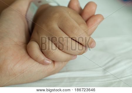 Hands of littel boy and hands of mother wristband barcode in hospital bed