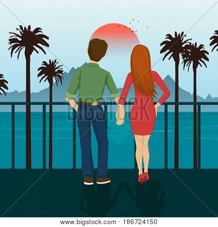 Young couple holding hands standing on the seafront, looking at sunset. Mountains, sea, ocean, palm trees, seacoast