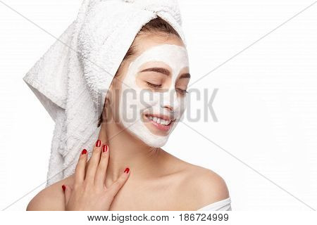 Beautiful woman enjoying on white background with cleansing mask on face.
