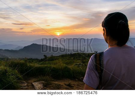 Woman tourist looking beautiful nature of colorful sky during the sunset over the mountain at view point Phu Chi Fa Forest Park in Chiang Rai Province Thailand