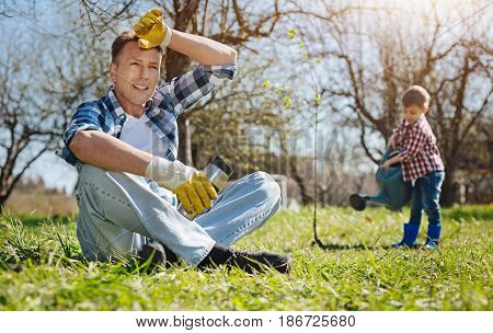 What a busy day. Shot of a mature man holding a thermos mug, sitting on the grass and having a rest while his son watering a tree on the background