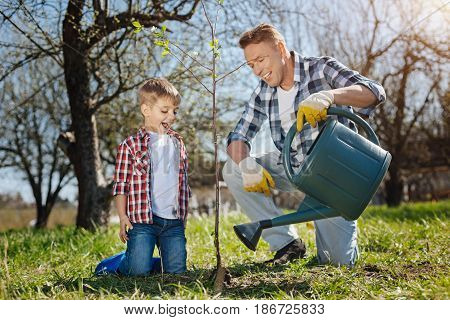 Taking care of nature. Happy father watering a newly planted tree with his adorable son while both standing on knees in a sunny spring day