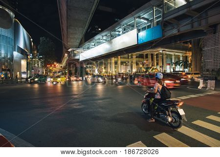 Night city traffic of cars and motorbikes moves slowly along a busy highway road with subway above the road near the city center in Bangkok, Thailand, cityscape photography.