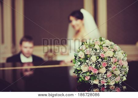 Pink wedding bouquet lies on the piano while groom plays for a bride