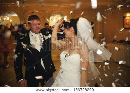 Groom Whirls A Bride In The Rain Of White Confetti