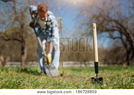 Taking care of environment. A shot of a mature guy gardening in spring, planting a new tree and a digging soil scoop in front