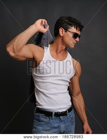 the attractive biker is holding on to his shirt.