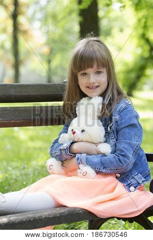 Little Girl Sits On A Bench And Holding In The Hands Of Her Favorite Stuffed Toy
