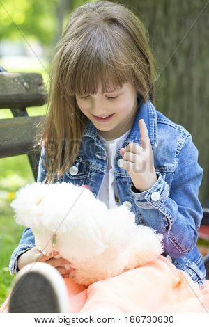 Little Girl Sitting On The Bench And Plays With His Favorite Stuffed Toy