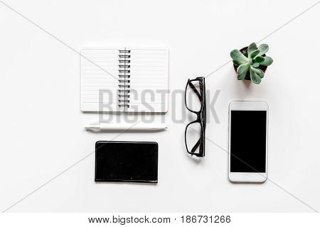 Modern office table with mobile phone, glasses, notebook on white background top view mock-up